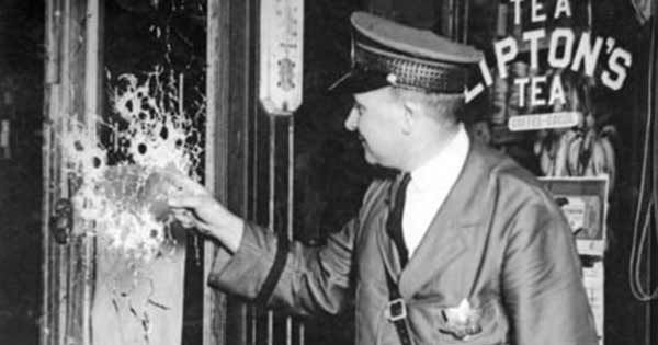 CPD officer inspect bullet holes in a window